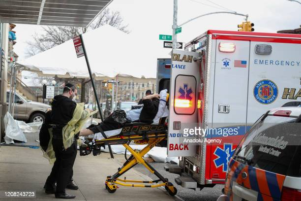 A patient with a face mask is being carried to an ambulance at the Maimonides Medical Center in Brooklyn New York United States on March 25 2020 The...