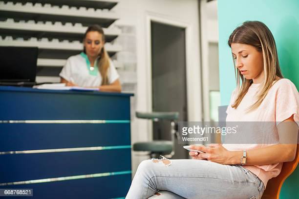 Patient with smart phone waiting in dentists waiting room