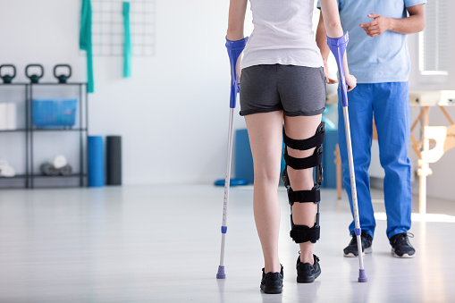 Patient with stiffener on the leg walking with crutches during rehabilitation 1034949288