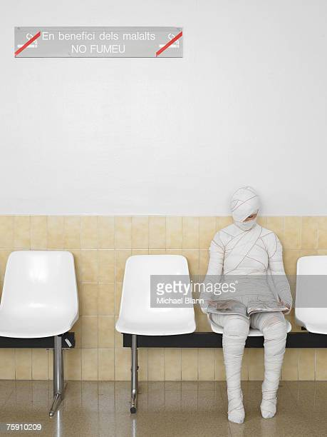 Patient wrapped in bandages, seated in waiting room