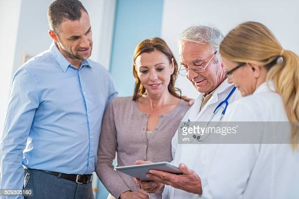Patients and doctors examining test results on a digital tablet