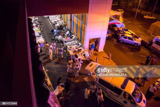 TOPSHOT Patients and employees wait to be dispatched to other hospitals outside the University Hospital of PointeaPitre in the French overseas island...