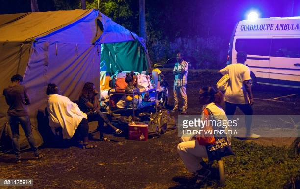 Patients and employees wait to be dispatched to other hospitals outside the University Hospital of PointeaPitre in the French overseas island of...