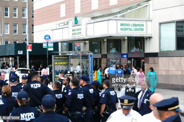 Patients and hospital staff walk past police outside the BronxLebanon Hospital as they respond to an active shooter north of Manhattan in New York on...