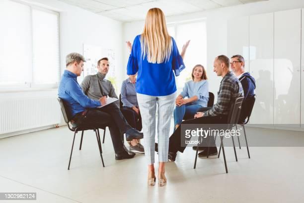 pazienti e istruttore che ascoltano la donna matura - izusek foto e immagini stock