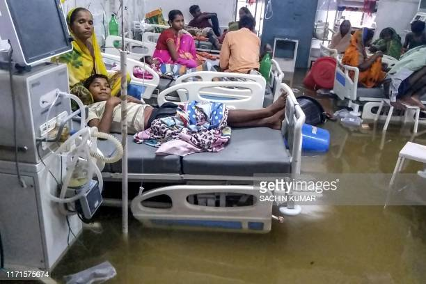 TOPSHOT Patients and their relatives rest in beds as they wade through floodwaters during heavy monsoon rain at waterlogged Nalanda Medical College...