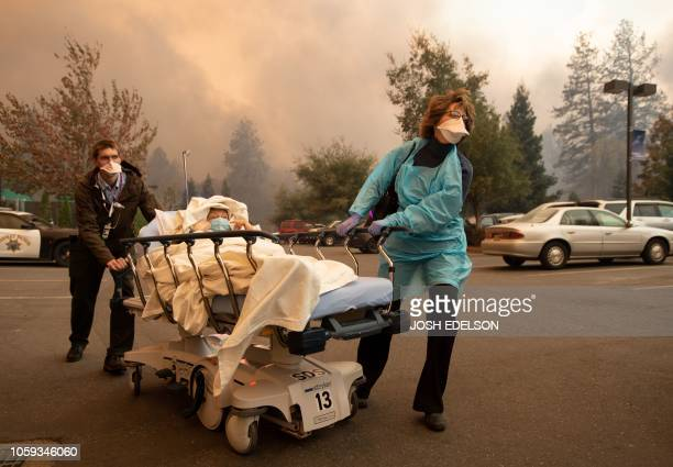 Patients are quickly evacuated from the Feather River Hospital as it burns down during the Camp fire in Paradise, California on November 8, 2018. -...