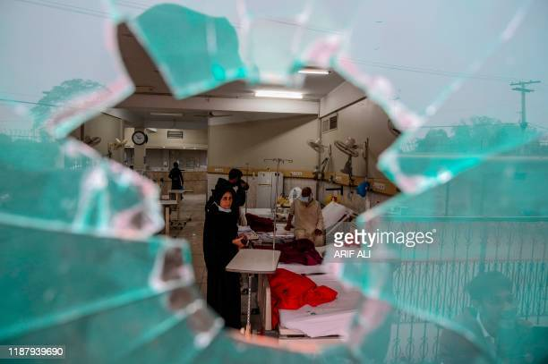 Patients are seen through a broken window of a cardiac hospital following an attack by lawyers in the premises in Lahore on December 11, 2019. - At...