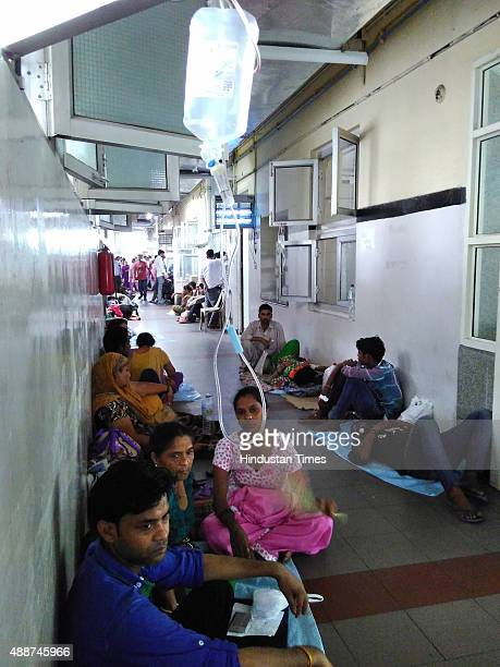 Patients as well as their families sit outside the dengue ward due to the shortage of beds at Safdarjung Hospital on September 17 2015 in New Delhi...