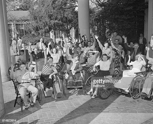 Patients at the Warm springs Foundation wave as President Roosevelt arrived November 29th for a brief visit which was cut short 26 hours later by a...
