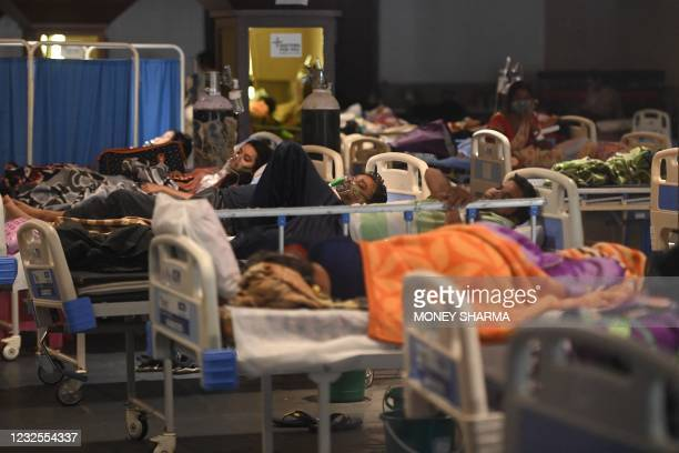Patients breath with the help of oxygen masks inside a banquet hall temporarily converted into a Covid-19 coronavirus ward in New Delhi on April 27,...