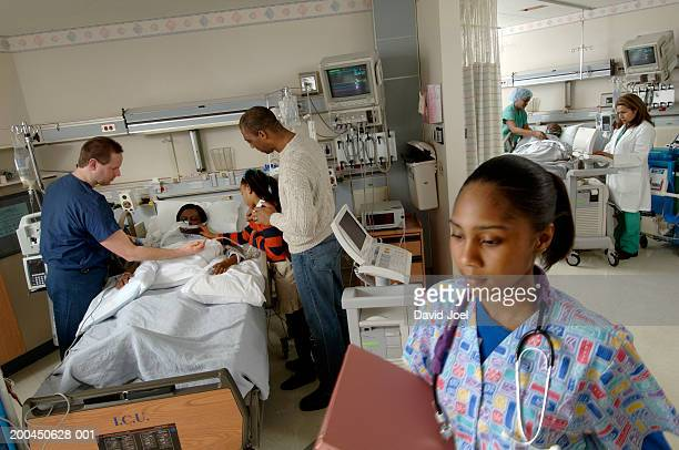 patients, doctors and visitors in intensive care unit, elevated view - patient on ventilator stock pictures, royalty-free photos & images