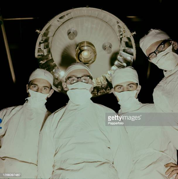 Patient's eye view of student doctors, all wearing white surgical gowns and masks, grouped around an operating theatre bed during training at Charing...