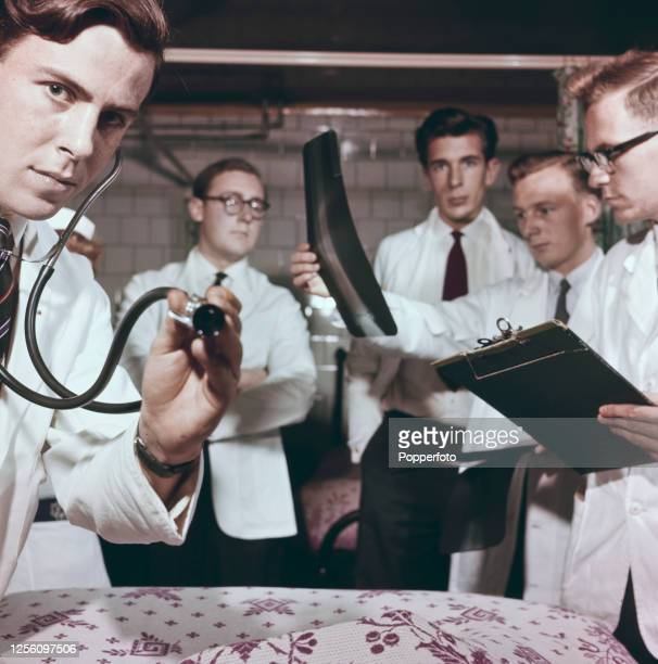 A patient's eye view of student doctors one holding a stethoscope and another looking at a radiograph grouped around a hospital bed at Charing Cross...