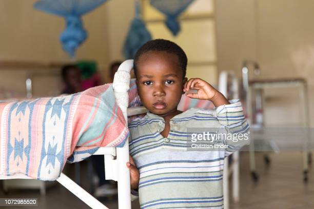 Patients, here a boy in a hospital in Zimbabwe, in the background a hospital bed can be seen.