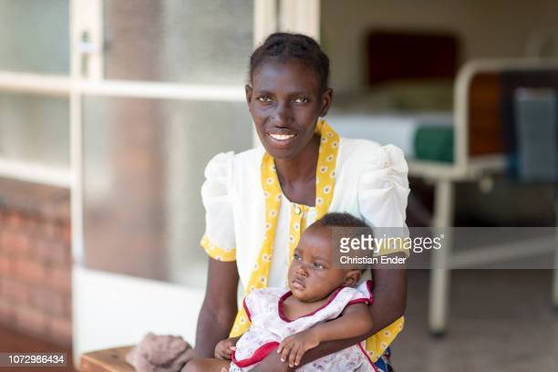 Patients here a mother with her child in a hospital in Zimbabwe in the background a hospital bed can be seen