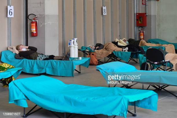 Patients lie in bed at a temporary emergency structure set up outside the accident and emergency department where any new arrivals presenting suspect...