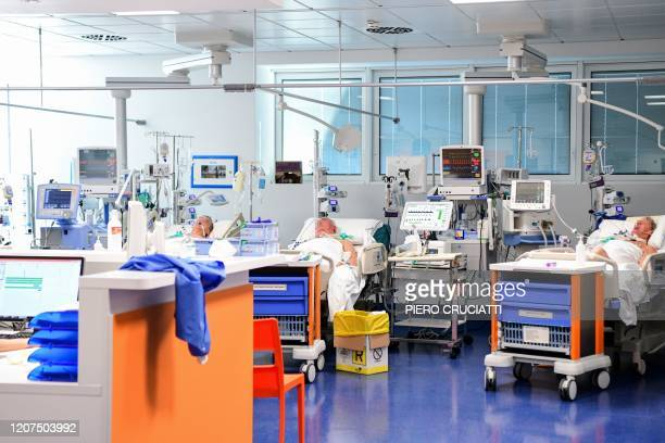 Patients lie in bed inside the new coronavirus intensive care unit of the Brescia Poliambulanza hospital Lombardy on March 17 2020
