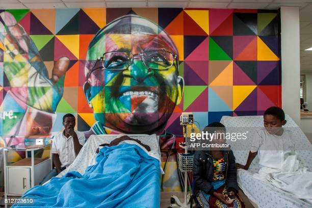 Patients lie in beds under a mural depicting South African bishop Desmond Tutu in the Mercy James Children's Hospital during its opening ceremony at...