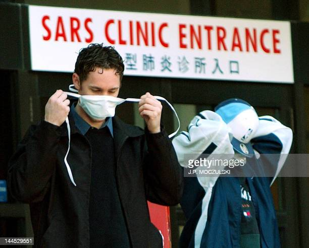 Patients put on face masks as they leave the SARS clinic setup at Sunnybrook & Women's hospital in Toronto, Canada, on 31 March, 2003. Canada has...