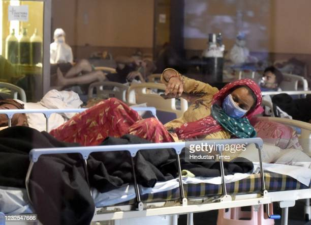 Patients rest at the Covid-19 Care Centre, for a temporary Covid Care Centre set up at Shehnai Banquet Hall attached to LNJP Hospital, on April 26,...