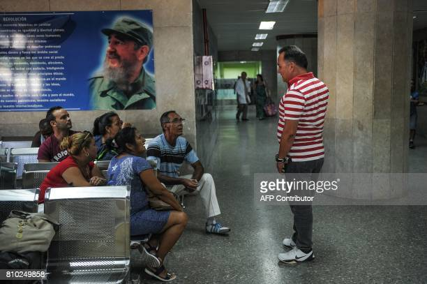 Patients sit in a waiting room near a poster of late Cuban leader Fidel Castro at the Comandante Manuel Fajardo Hospital in Havana on July 6 2017 /...
