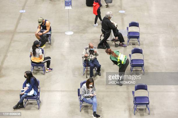 Patients sit in an observation area after receiving the Pfizer Covid-19 vaccine during opening day of the Community Vaccination Site, a collaboration...