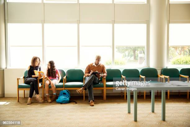 patients sitting on chairs in waiting room - outpatient care stock pictures, royalty-free photos & images