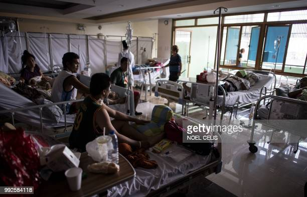 Patients suffering from leptospirosis receive treatment at the East Avenue Medical Center in Manila on July 6, 2018. - Health officials have said...