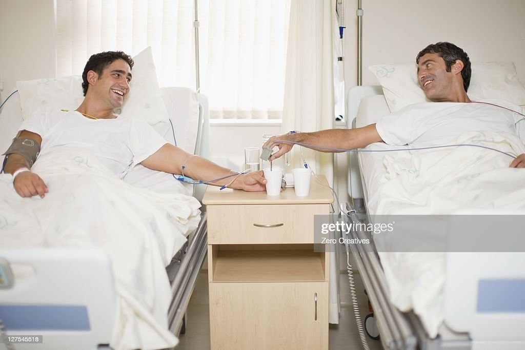 Patients talking in hospital beds : Stock Photo