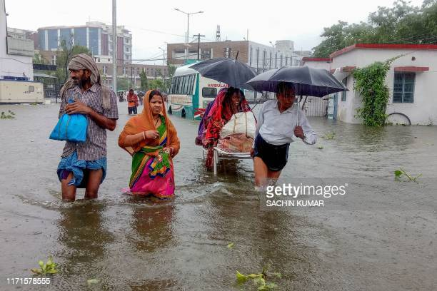 TOPSHOT Patients wade through floodwaters on their way to hospital during heavy monsoon rain in Patna in the northeastern state of Bihar on September...