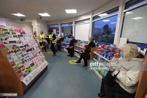 Patients wait in a socially-distanced queue ahead of receiving an injection of the coronavirus Covid-19 vaccine at Andrews Pharmacy in Macclesfield,...
