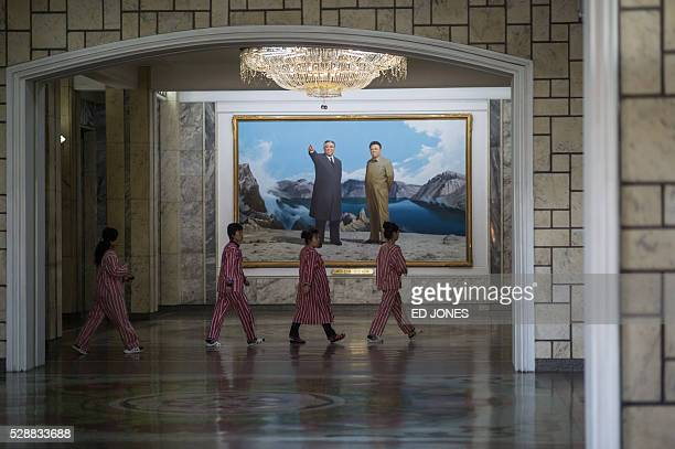 Patients walk thorugh a hallway past a portrait of late North Korean leader Kim IlSung and Kim JongIl at the Pyongyang Maternity Hospital during a...