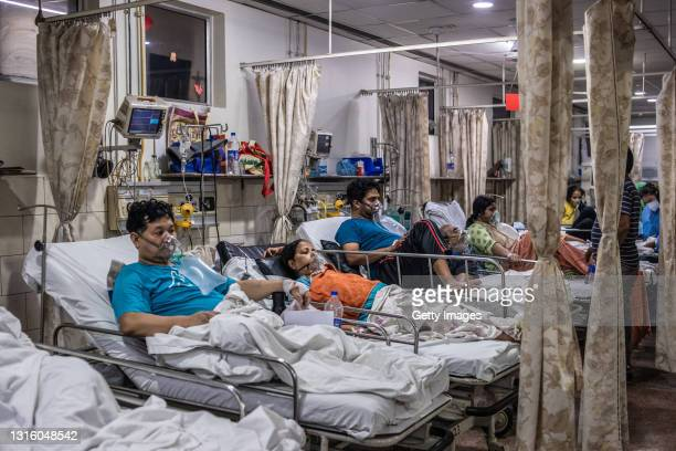 Patients who contracted the coronavirus lie in beds while connected to oxygen supplies inside the emergency ward of a Covid-19 hospital on May 03,...