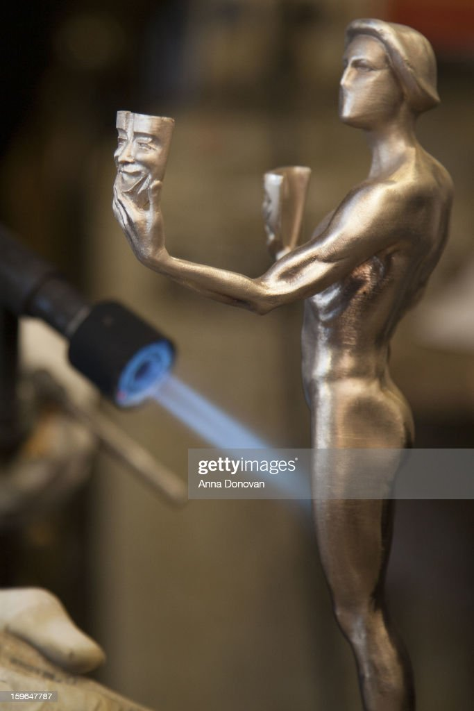 Patina artist Paul Napier puting a finishing touch on one of the bronze Screen Actors Guild Award statuettes at the American Fine Arts Foundry on January 17, 2013 in Burbank, California.