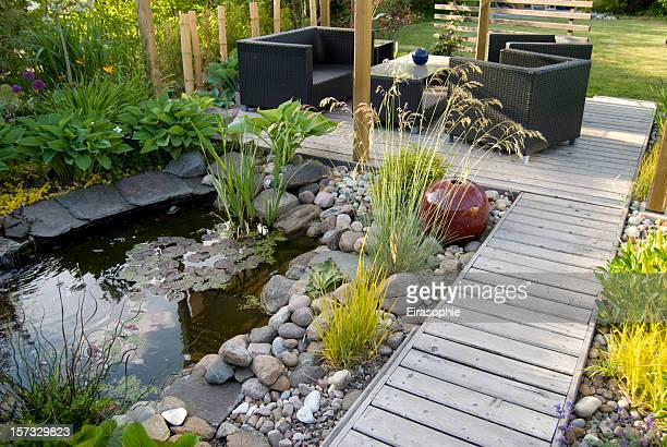 patio and pond in the afternoon sun - landscaped stock pictures, royalty-free photos & images