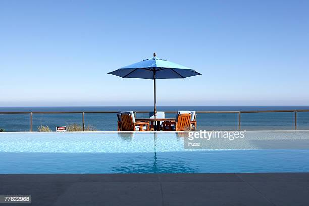 Patio Furniture under Umbrella by Swimming Pool on Oceanfront