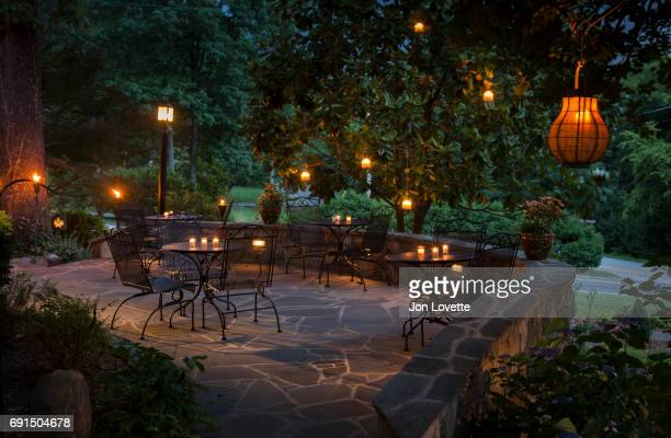Patio lit with hanging lanterns and candles
