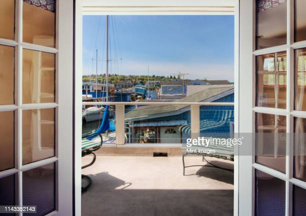 patio overlooking boats in dock - french doors stock pictures, royalty-free photos & images
