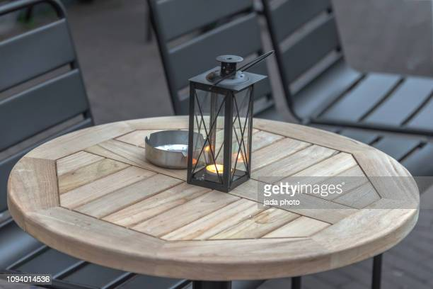patio table and chairs with an ashtray and a candle holder on the table - candlestick holder stock pictures, royalty-free photos & images
