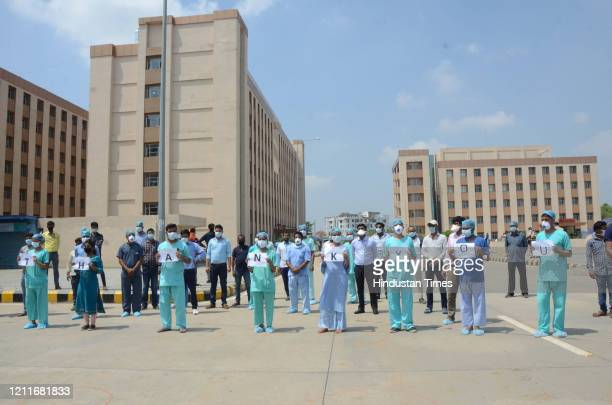 PatnaMay32020Doctors nurses and other medical professionals react as an Indian Air Force chopper approach to shower flower petals over Patna AIIMS to...