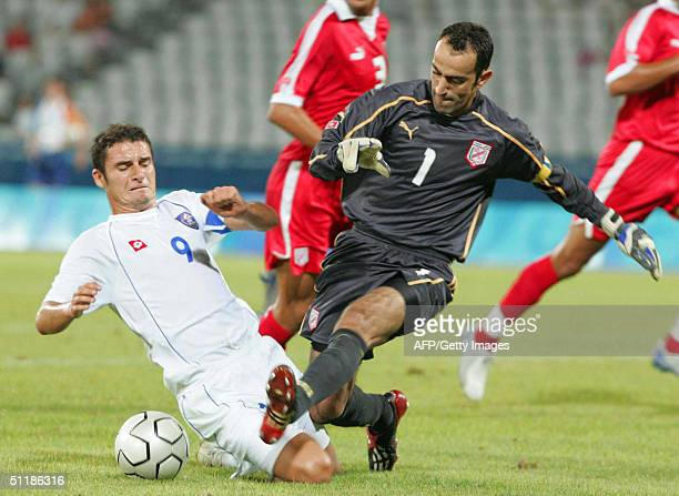 Tunisia's Khaled Fadhel fights for the ball with Andrija Delibasic of SerbiaMontenegro during their Olympic Games men's group C preliminary football...