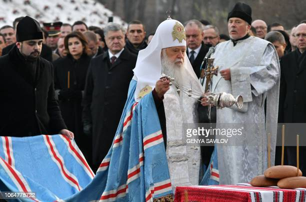 Patriarch Filaret of the Ukrainian Orthodox Church of Kiev's Patriarchate conducts a prayer during a commemoration ceremony at a monument to victims...