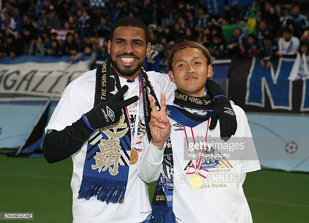 Patric and Takashi Usami of Gamba Osaka pose for photographs with the trophy after winning the 95th Emperor's Cup final between Urawa Red Diamonds...