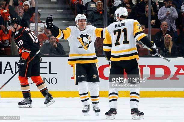 Patric Hornqvist and Evgeni Malkin of the Pittsburgh Penguins celebrate a goal in the first period against Corey Perry of the Anaheim Ducks during...