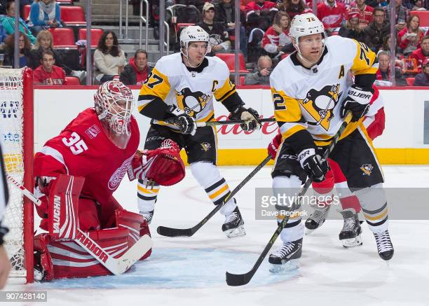 Patric Hornqvist and Sidney Crosby of the Pittsburgh Penguins sets up in front of Jimmy Howard of the Detroit Red Wings during an NHL game at Little...