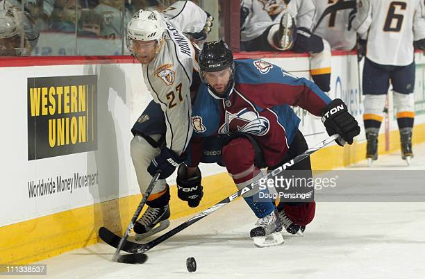 Patric Hornqvist of the Nashville Predators and Philippe Dupuis of the Colorado Avalanche battle for control of the puck at the Pepsi Center on March...