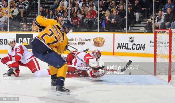 Patric Hornqvist of the Nashville Predators puts the puck in the net against goalie Joey MacDonald of the Detroit Red Wings during an NHL game at the...