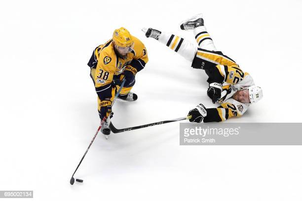 Patric Hornqvist of the Pittsburgh Penguins and Viktor Arvidsson of the Nashville Predators battle for the puck during the third period in Game Six...
