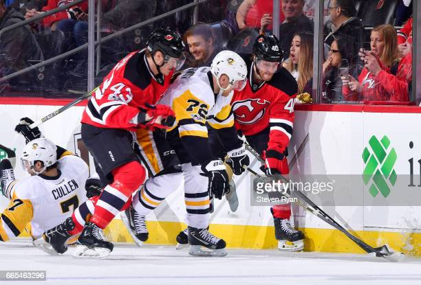 Patric Hornqvist of the Pittsburgh Penguins battles for the puck along the boards against Blake Coleman of the New Jersey Devils and Ben Thomson...